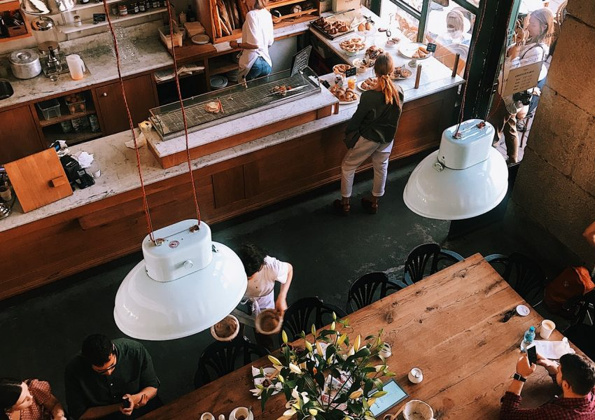 birds eye view of timber cafe with long table and hanging lights