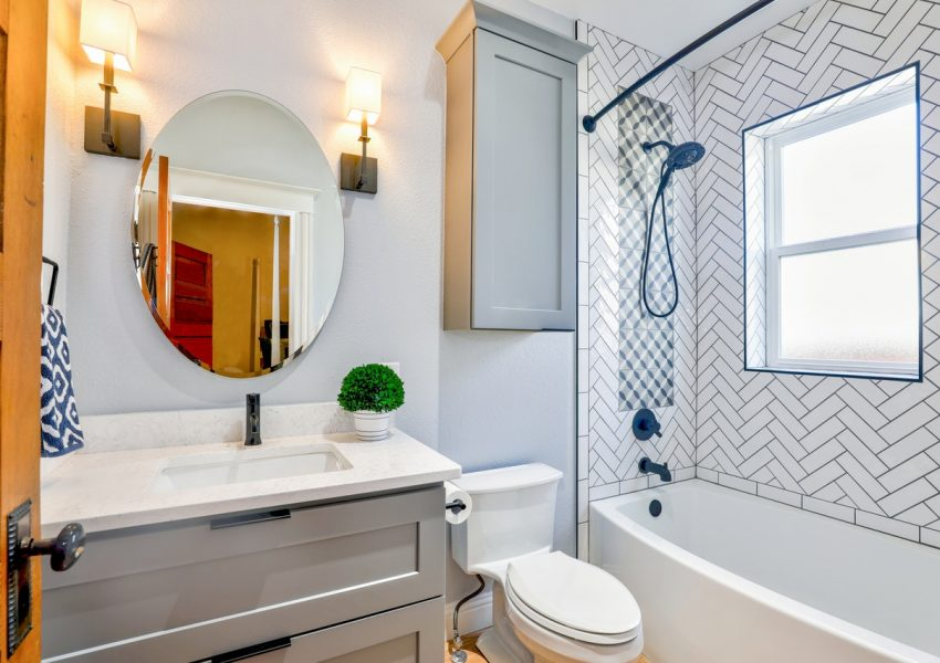 pretty bathroom with white bath and sink with a circle mirror